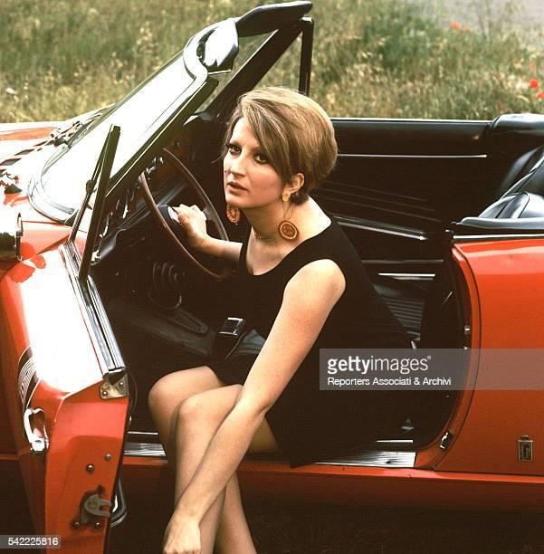 Italian singer Mina sitting on a sport car during the Summer Autoraduno Italy 1968