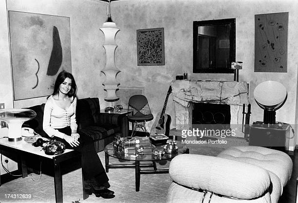Italian singer Nada sitting in the livingroom at home The room is furnished with some paintings and many design objects Rome 1970s