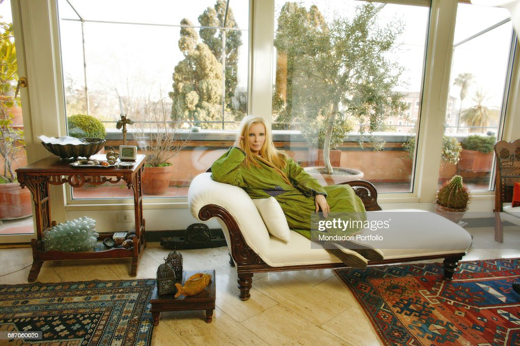 Italian singer Patty Pravo (Nicoletta Strambelli) relaxing on a sofa in her house in Rome. Rome, 1990s