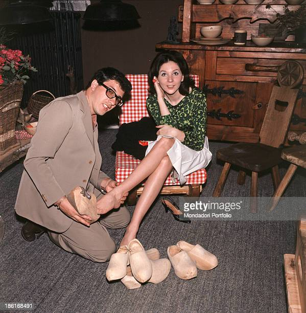 Italian singer Peppino di Capri putting a clog on his wife Roberta Stoppa's foot 1964