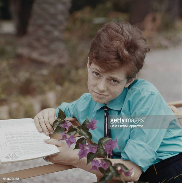 Italian singer Rita Pavone pictured wearing a blue shirt tie and pleated skirt and holding a book circa 1964