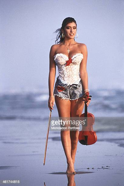 Italian singer showgirl and actress Sabrina Salerno walking on the seashore with a violin Italy 1988