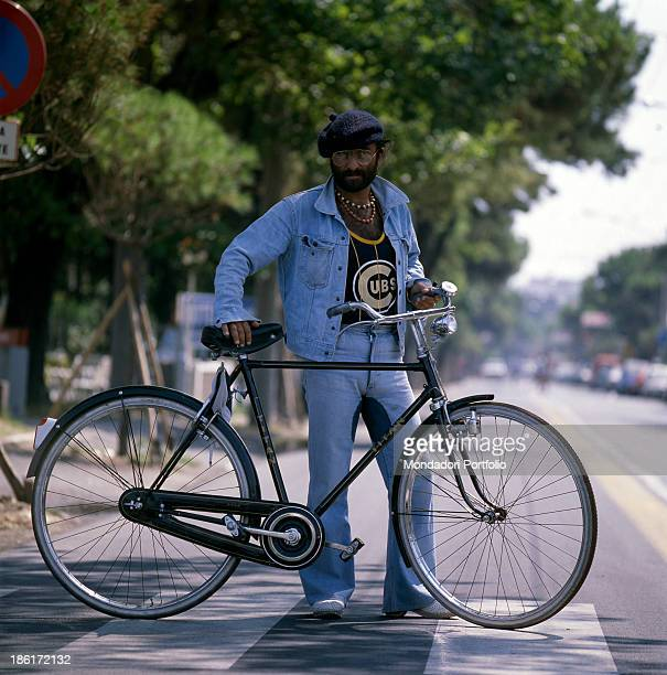 Italian singer, songwriter and musician Lucio Dalla posing on a pedestrian crossing leaning on a bicycle. 1980.