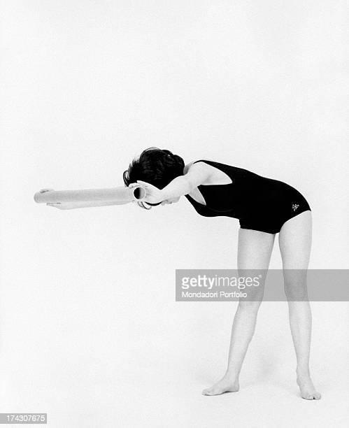 Italian singer Stella Dizzy bending forward holding a tube 1960s