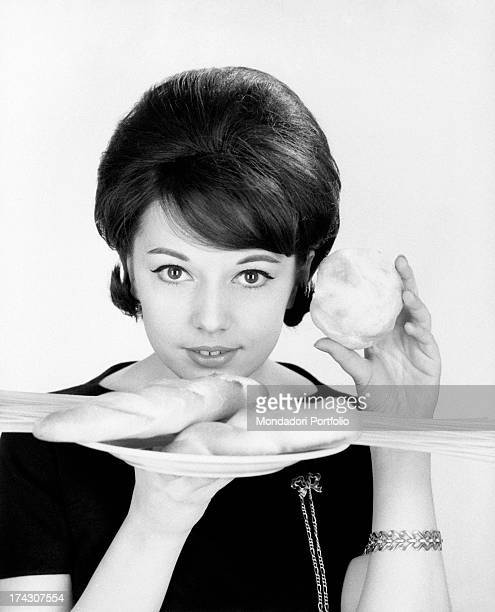 Italian singer Stella Dizzy holding a and a plate with bread and spaghetti 1960s