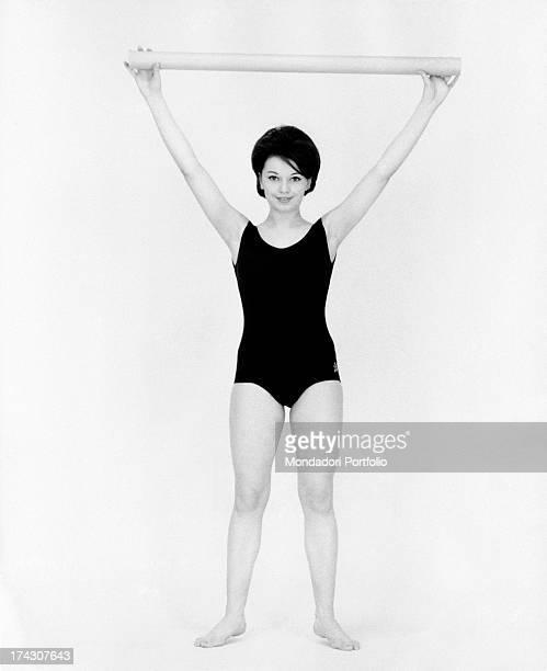 Italian singer Stella Dizzy raising a tube 1960s