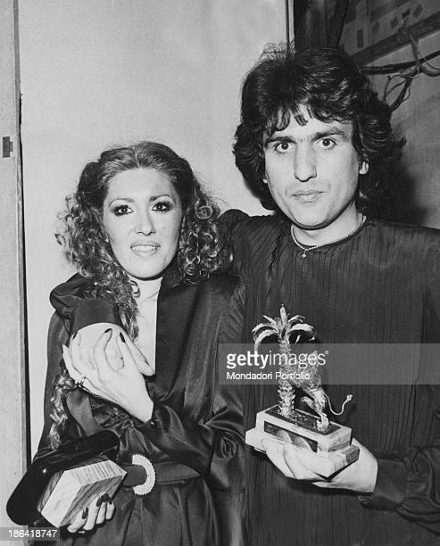 Italian singer Toto Cutugno hugging his wife Carla and holding the prize won with the song Solo noi at 30th Sanremo Music Festival Sanremo February...