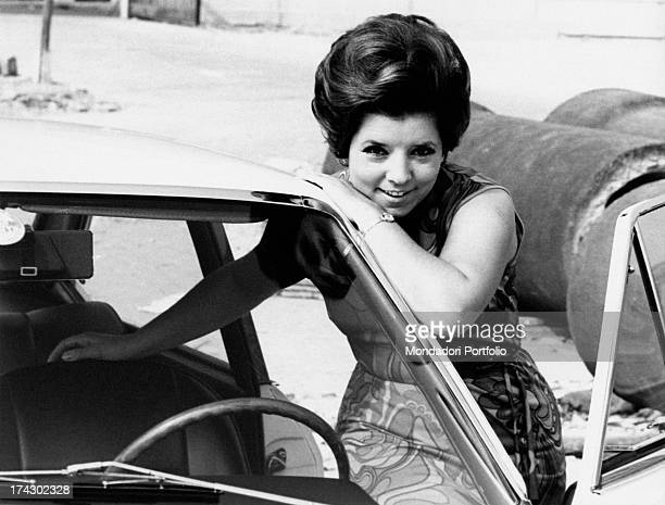 Italian singer Wilma De Angelis going into the car her right hand rests on the front seat while her left arm lies on the windscreen October 1967