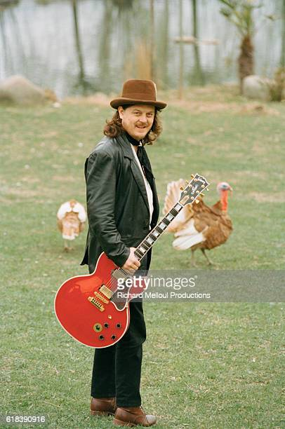 Italian singer Zucchero Fornacieri holding a red electric guitar Behind him two turkeys wander the grounds of his farm in Pontremoli