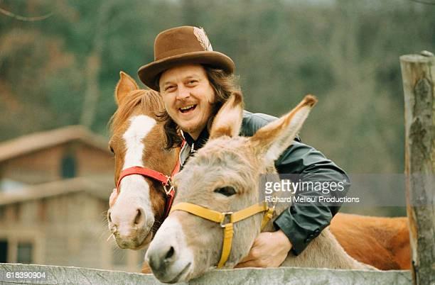 Italian singer Zucchero Fornacieri hugs a horse and a donkey on his farm in Pontremoli