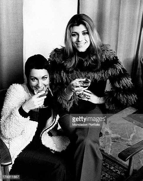 Italian singers and members of the band Ricchi e Poveri Marina Occhiena and Angela Brambati posing smiling with a glass of champagne in the hand...