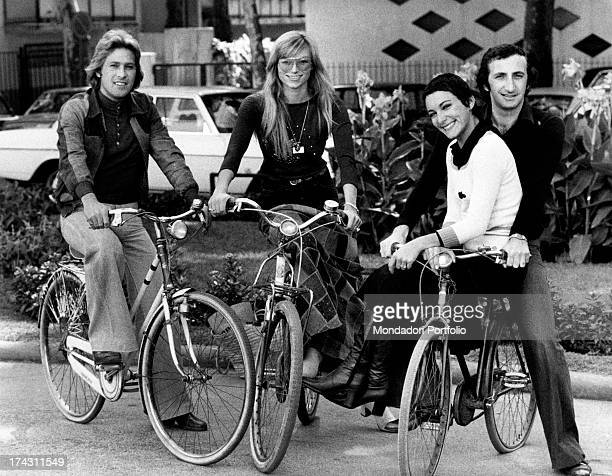 Italian singers Marina Occhiena Angela Brambati Angelo Sotgiu and Franco Gatti posing on some bicycles during the International Pop Music Expo They...