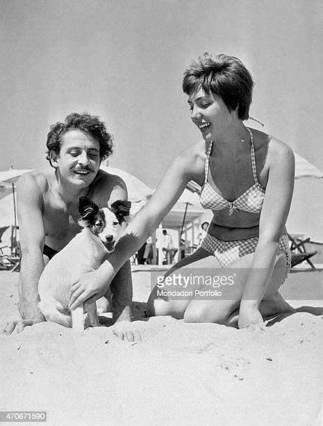 'Italian singersongwriter actor and director Domenico Modugno and his wife and Italian singer and actress Franca Gandolfi playing with their dog at...