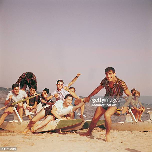 Italian singersongwriter and actor Adriano Celentano dragging a young man sitting on a pedalo with some other people Italy 1962