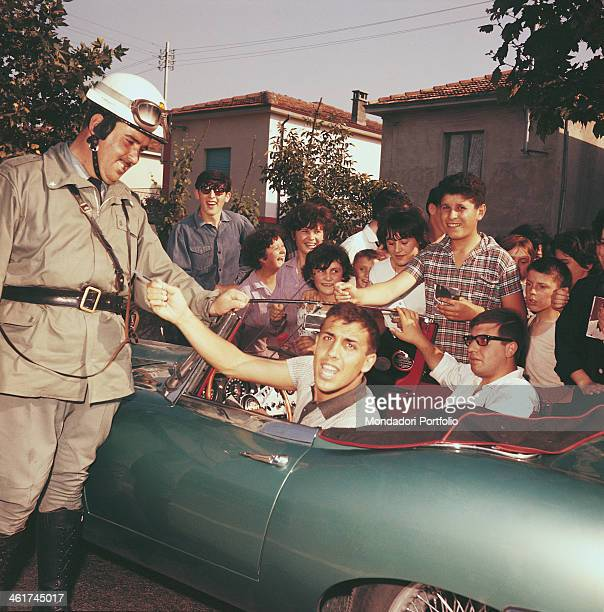 Italian singersongwriter and actor Adriano Celentano sitting in his car surrounded by a group of young fans rushed up to attend the festival...
