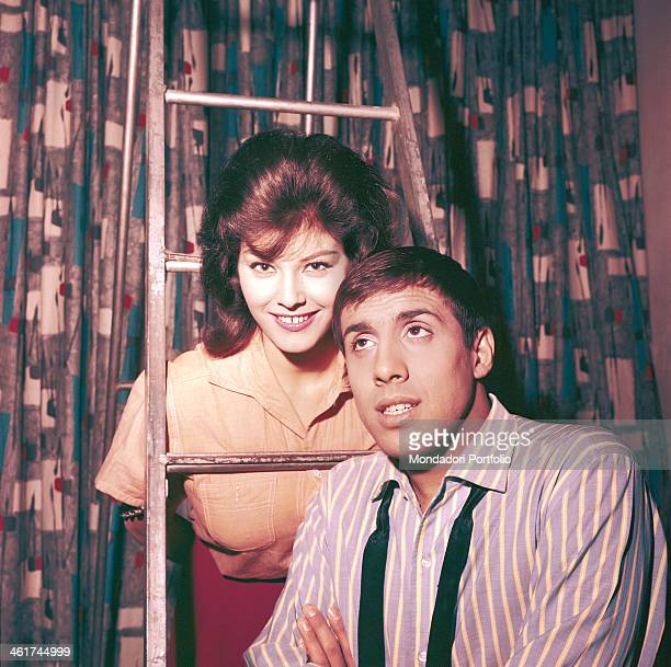 Italian singersongwriter and actor Adriano Celentano sitting on a ladder while his future wife Italian actress singer and record producer Claudia...