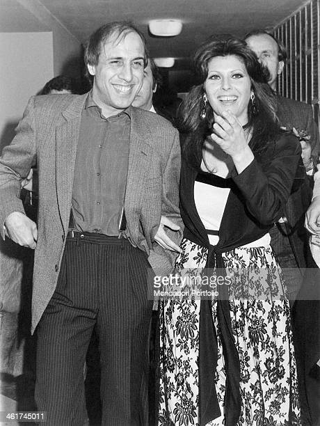 Italian singersongwriter and actor Adriano Celentano walking arm in arm with his wife Italian actress singer and record producer Claudia Mori called...
