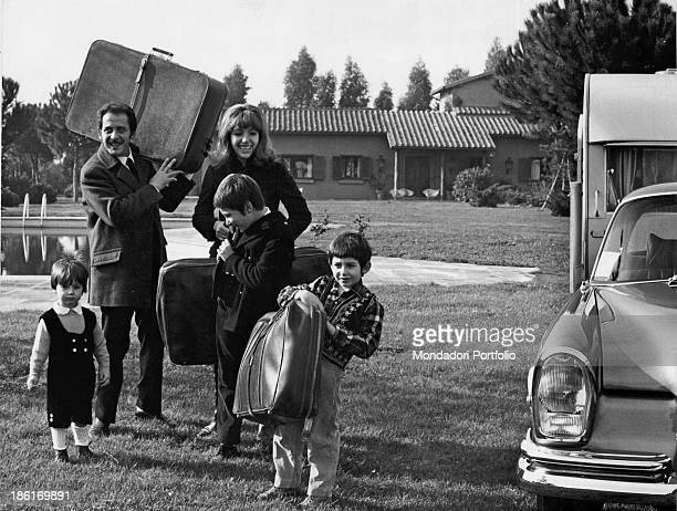 Italian singersongwriter and actor Domenico Modugno carrying a suitcase with his wife Italian actress and singer Franca Gandolfi and their children...