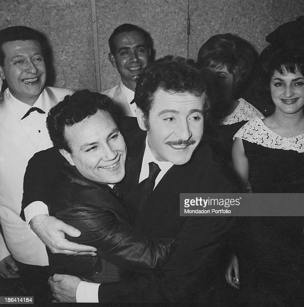 Italian singer-songwriter and actor Domenico Modugno hugging Italian singer and actor Claudio Villa during the 12th Sanremo Music Festival. They both...