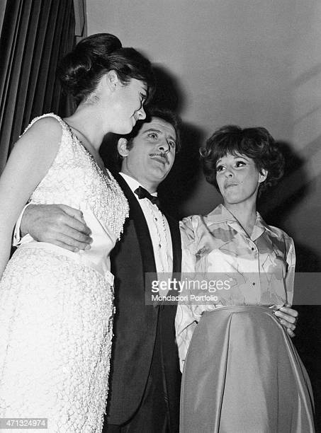 Italian singersongwriter and actor Domenico Modugno hugging Italian singers Gigliola Cinquetti and Ornella Vanoni at 16th Sanremo Music Festival...