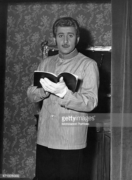 Italian singersongwriter and actor Domenico Modugno in porter's uniform holding a book 1950s