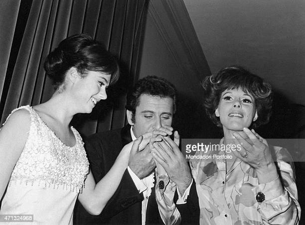 Italian singersongwriter and actor Domenico Modugno kissing Gigliola Cinquetti and Ornella Vanoni's hands at 16th Sanremo Music Festival Sanremo...