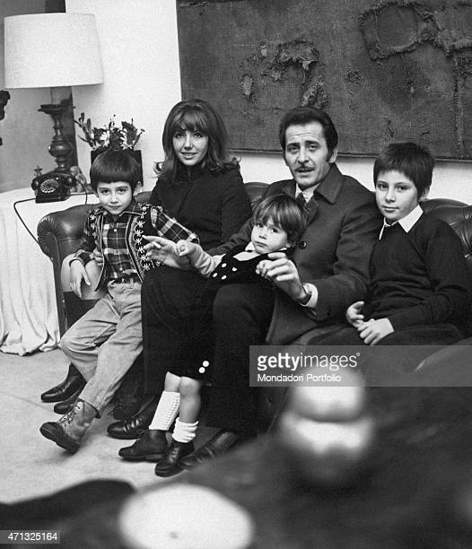 Italian singersongwriter and actor Domenico Modugno posing seated on a sofa at home beside his wife and Italian actress Franca Gandolfi and his sons...