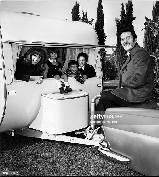 Italian singersongwriter and actor Domenico Modugno smiling sitting on a car His wife the Italian actress and singer Franca Gandolfi with their...
