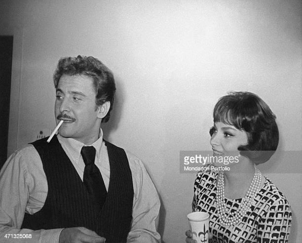 Italian singersongwriter and actor Domenico Modugno smoking a cigarette beside Italian actress Gina Lollobrigida 1960s