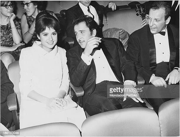 Italian singersongwriter and actor Domenico Modugno smoking a cigarette sitting beside Italian actress and singer Gigliola Cinquetti at the 16th...