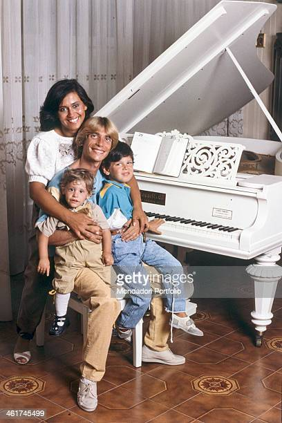 Italian singersongwriter and actor Nino D'Angelo posing smiling sitting in front of a piano with his wife Annamaria Gallo and their children Antonio...