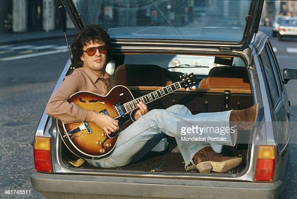 Italian singersongwriter and composer Ivano Fossati playing the guitar seated in a car boot Italy 1979