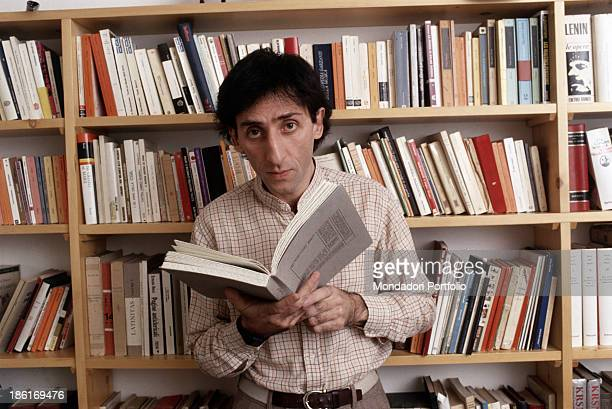 Italian singersongwriter and director Franco Battiato holding a book in his hands in front of a bookcase 1981