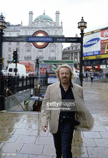 Italian singersongwriter and guitarist Umberto Tozzi walking in Piccadilly Circus Behind him the entrance of the underground the London Pavillion...