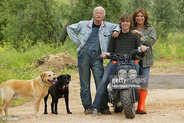 Italian singersongwriter and musician Gino Paoli posing in his farm in Maremma with his Italian son Tomaso Paoli on a scooter his Italian wife Paola...