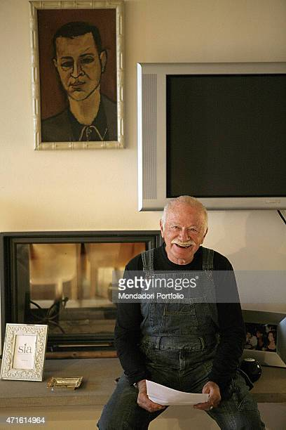 'Italian singersongwriter and musician Gino Paoli smiling seated in the livingroom of his farm in Maremma in front of a painting made by himself...