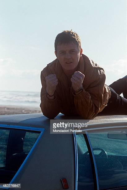 Italian singersongwriter and musician Zucchero posing lying on a car roof showing his clenched fists Italy 1985