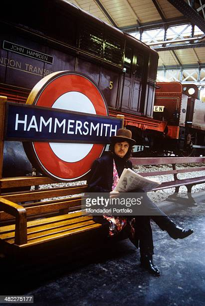 Italian singersongwriter and musician Zucchero reading a newspaper seated on a bench at Hammersmith station London 1989