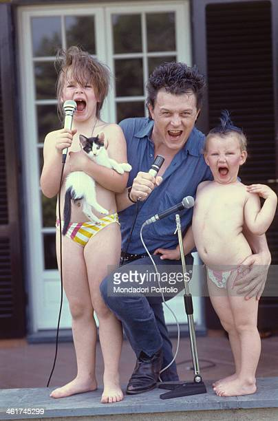Italian singersongwriter and musician Zucchero singing for fun into the microphone with his daughters Irene and Alice holding a cat in her arms Italy...