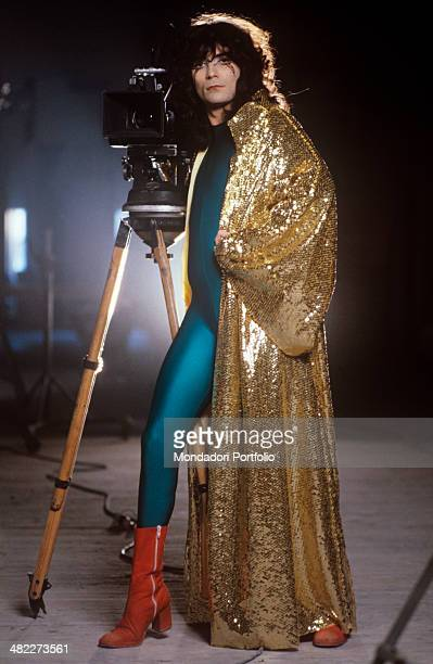 Italian singersongwriter and showman Renato Zero wearing a tight bluegreen suit and a golden sequin cloak posing on the set of the film Ciao nì...