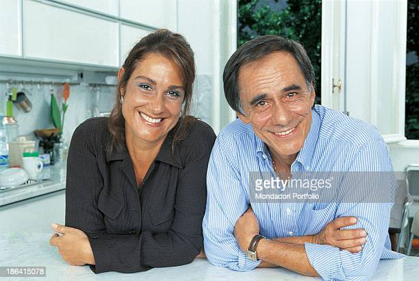 Italian singersongwriter and writer Roberto Vecchioni and his wife Italian journalist Daria Colombo posing smiling leaning on the table of the...