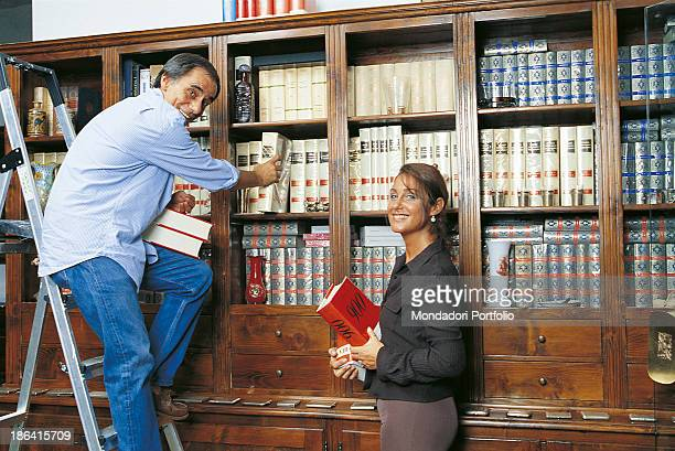 Italian singersongwriter and writer Roberto Vecchioni and his wife Italian journalist Daria Colombo putting some books in the bookcase of their new...