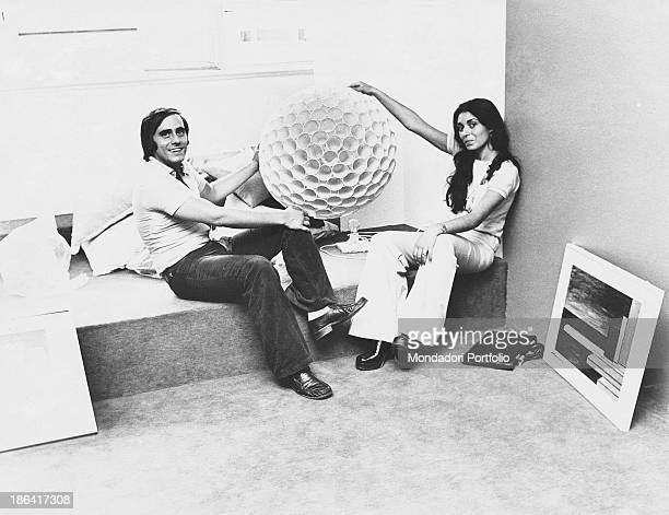 Italian singersongwriter and writer Roberto Vecchioni holding a design object in his hands with his girlfriend Irene Bozzi Milan 1973