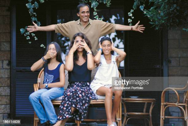 Italian singersongwriter and writer Roberto Vecchioni opening his arms behind his wife Italian journalist Daria Colombo and their daughters Francesca...