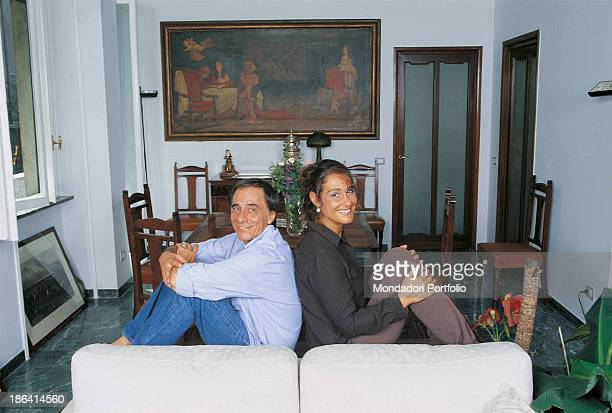 Italian singersongwriter and writer Roberto Vecchioni posing with his wife Italian journalist Daria Colombo on the sofa of their new flat Milan 2000