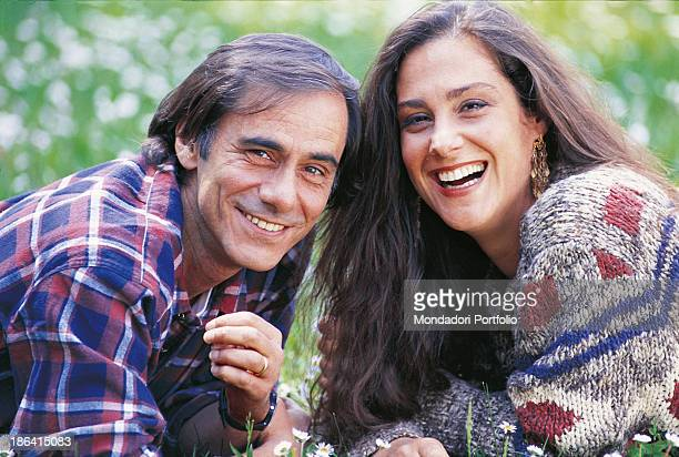 Italian singersongwriter and writer Roberto Vecchioni smiling on a meadow with his wife Italian journalist Daria Colombo Italy 1991