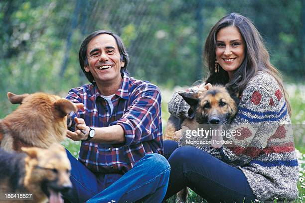 Italian singersongwriter and writer Roberto Vecchioni smiling sitting on a meadow with his wife Italian journalist Daria Colombo and some dogs Italy...