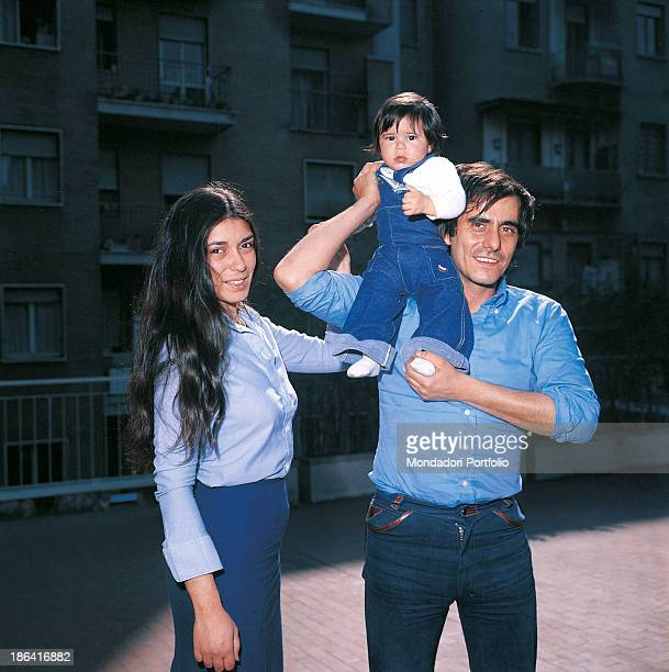 Italian singersongwriter and writer Roberto Vecchioni smiling with his wife Irene Bozzi holding his daughter Francesca in his arms Milan 1976