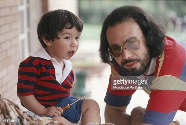 Italian singersongwriter Antonello Venditti posing with his son Francesco with a screwdriver in his hand 1978