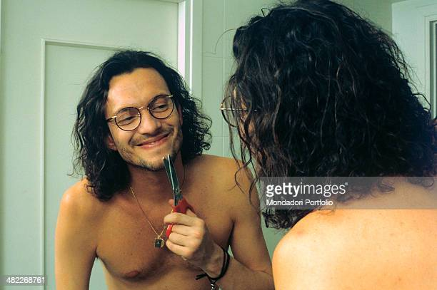 Italian singersongwriter Biagio Antonacci shaving himself with a pair of scissors at the 43rd Sanremo Music Festival Sanremo February 1993